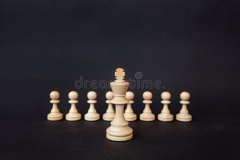 Schackstycken på en svart bakgrund De vita konungställningarna på bakgrunden av pantsätter arkivfoton