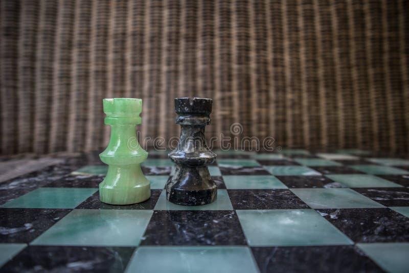 Schackstycken på marmorerar schackbrädet arkivbild