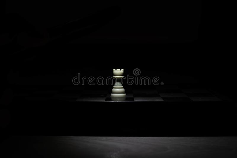 Schackstycken under ljuset i mörkret royaltyfri bild