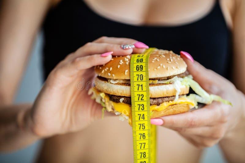 Schadelijk voedsel De keus tussen kwaadwillige voedsel en sport Mooi jong meisje op een dieet Het concept schoonheid en stock fotografie