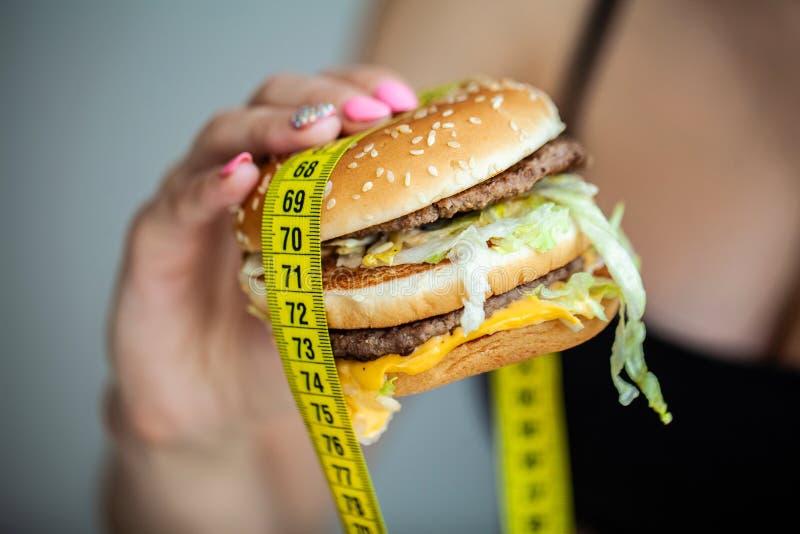 Schadelijk voedsel De keus tussen kwaadwillige voedsel en sport Mooi jong meisje op een dieet Het concept schoonheid en royalty-vrije stock afbeelding
