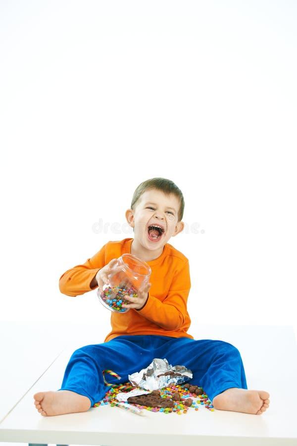 Schadelijke jongen met de zitting van de snoepjeskruik op vloer stock fotografie