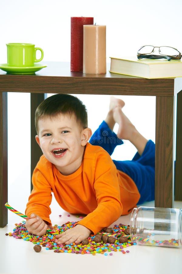 Schadelijke jongen met snoepjes en lolly thuis royalty-vrije stock afbeelding