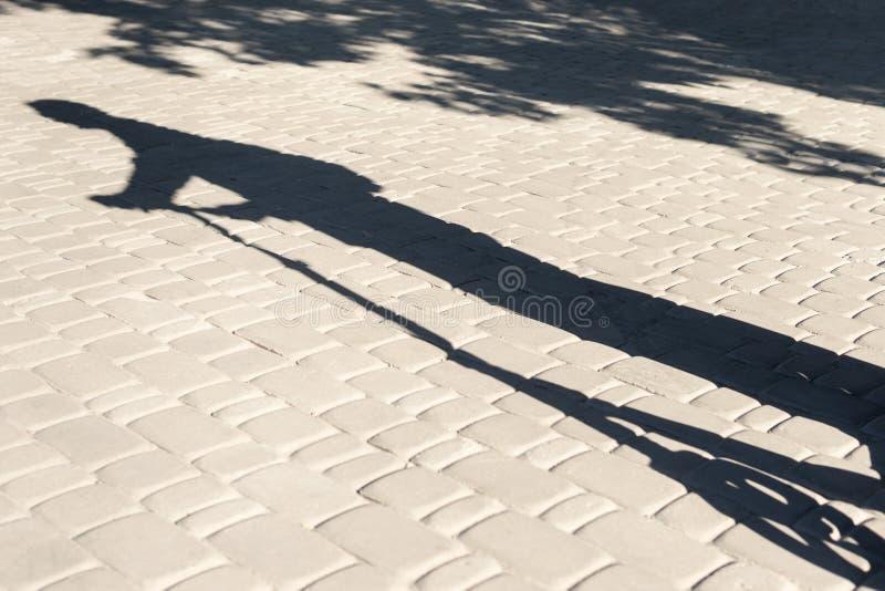 Schaduw van een mens op autoped stock fotografie