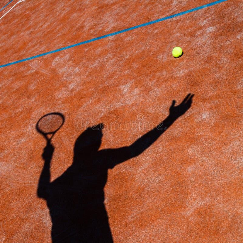 Schaduw van een tennisspeler in actie stock foto