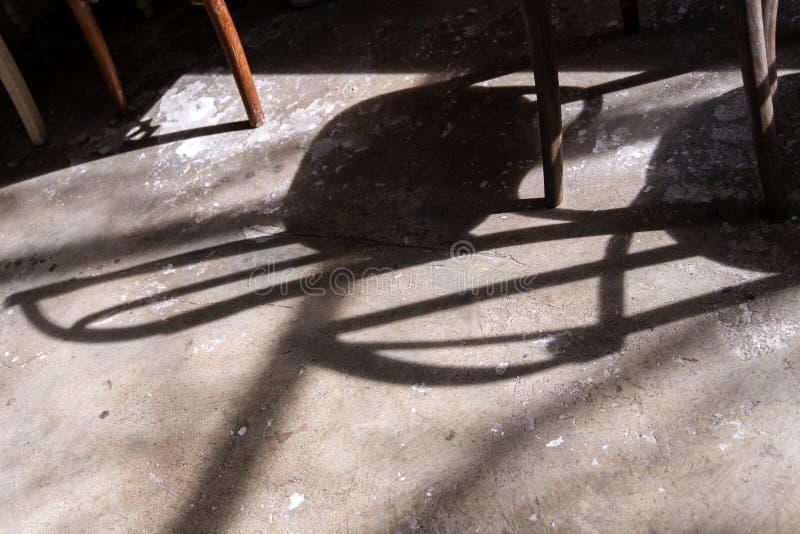 Schaduw van houten stoel op de vloer van het grungecement stock foto's