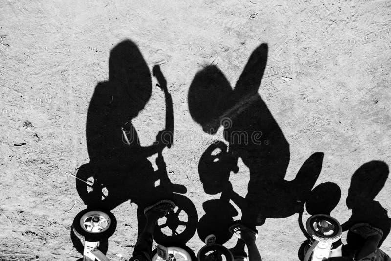 Schaduw van kinderen die een fiets in een dorp van Bali Indonesië berijden stock foto