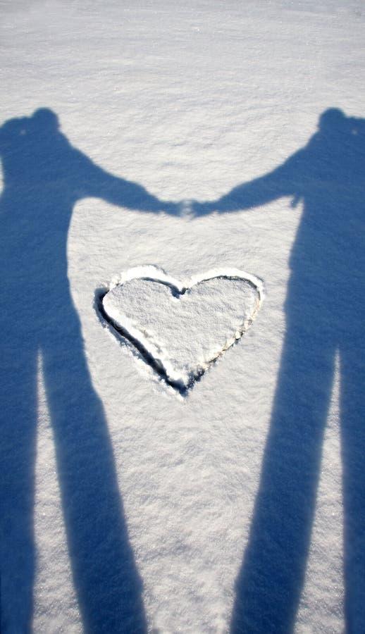 Schaduw van minnaars met hart op sneeuw royalty-vrije stock fotografie
