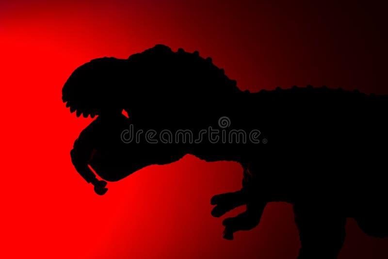 Download Schaduw Van Tyrannosaurus Die Een Menselijk Lichaam Met Rood Licht Bijten Stock Foto - Afbeelding bestaande uit eating, catching: 107706312