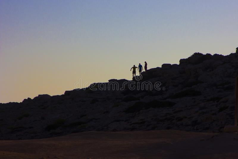 Schaduwen van mensen die zich aan de rots in het achterlicht vastklampen stock afbeeldingen