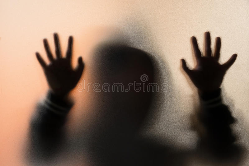 Schaduwonduidelijk beeld van de verschrikkingsmens in jasje met kap handen op het glas stock foto