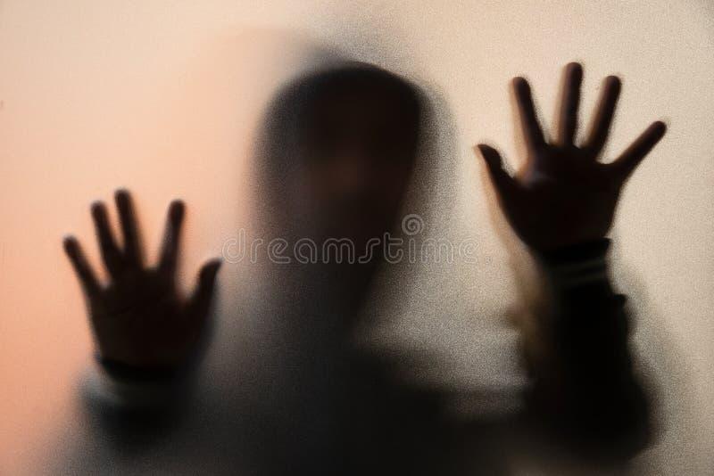 Schaduwonduidelijk beeld van de verschrikkingsmens in jasje met kap handen op het glas royalty-vrije stock foto