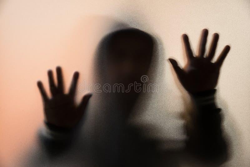 Schaduwonduidelijk beeld van de verschrikkingsmens in jasje met kap handen op het glas stock foto's