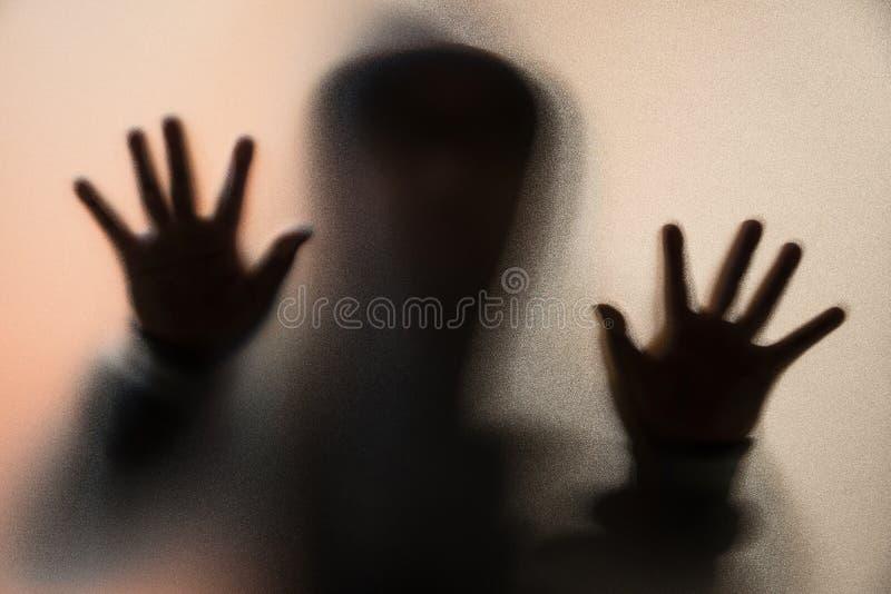 Schaduwonduidelijk beeld van de verschrikkingsmens in jasje met kap handen op het glas stock afbeelding