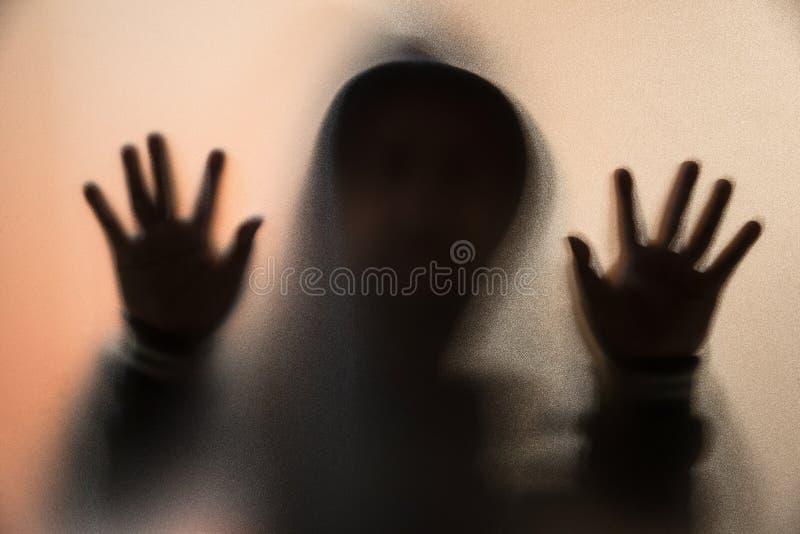 Schaduwonduidelijk beeld van de verschrikkingsmens in jasje met kap handen op het glas royalty-vrije stock afbeelding