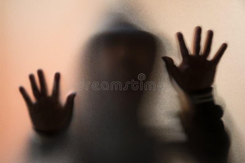 Schaduwonduidelijk beeld van de verschrikkingsmens in jasje met kap handen op het glas stock fotografie