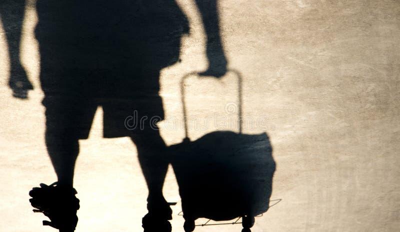 Schaduwsilhouet die van bejaarde een het winkelen karretjezak trekken stock fotografie