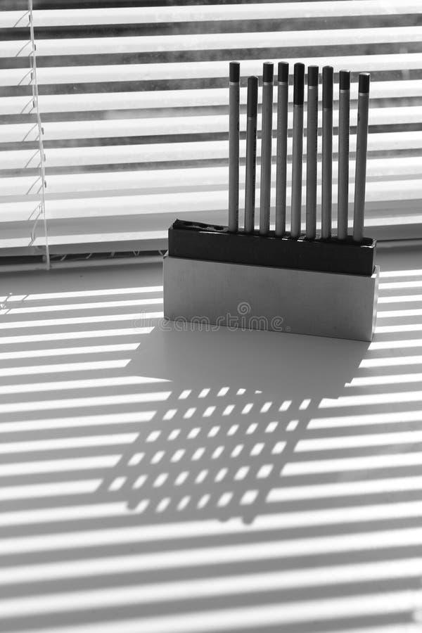Schaduwspel met potloden en zonneblinden royalty-vrije stock afbeeldingen