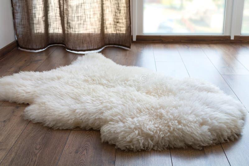Schaffell auf dem Laminatboden im Raum Gem?tlicher Platz nahe dem Fenster stockfoto