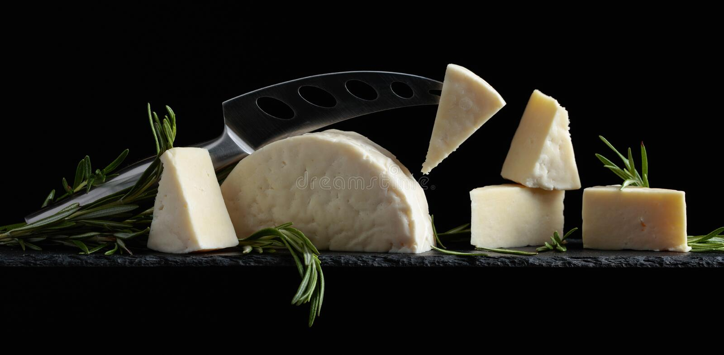Schafkäse mit Rosmarin auf einem schwarzen Hintergrund lizenzfreies stockbild