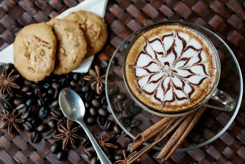 Schale Café Latte mit Kaffeebohnen und Plätzchen stockfotos