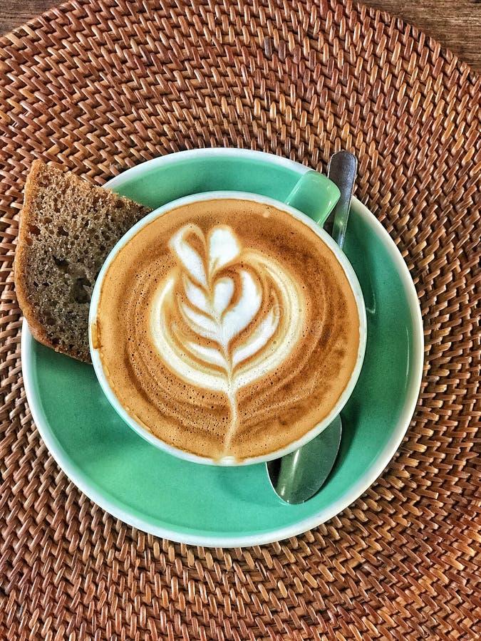 Schale Cappuccino mit Kaffeekunst und -brot lizenzfreie stockbilder