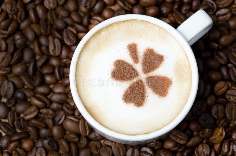 Schale Cappuccino mit Zimtmuster auf einem Hintergrund von coffe stockfoto