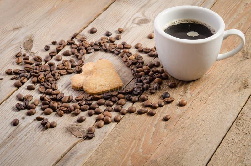 Schale coffe und Rahmen-Herz von den Kaffeebohnen und von Plätzchenherzen zwei lizenzfreies stockfoto