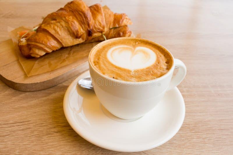 Schale des Cappuccinos und des H?rnchens stockfotografie