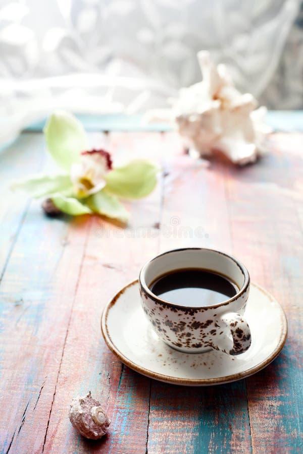 Schale des Espressosatzes mit einer Orchideenblume und -Muscheln stockfotos