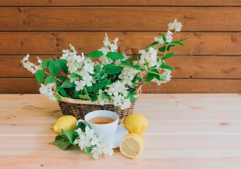 Schale des grünen Tees und des Korbes mit Jasmin blüht stockfotografie