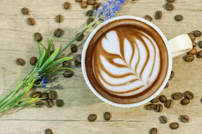 Schale des heißen Getränks des Espressos mit Kaffeestrahl und Lavendel blühen auf Holztisch lizenzfreie stockfotos