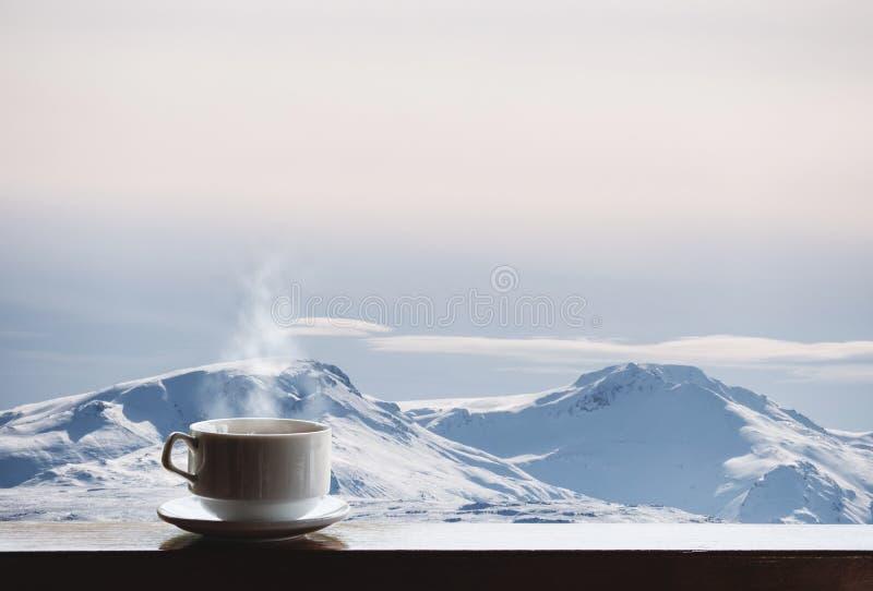 Schale des heißen Getränks mit Dampf auf hölzernem Schreibtisch und Schnee bedeckte Bergblick morgens mit einer Kappe stockfotos
