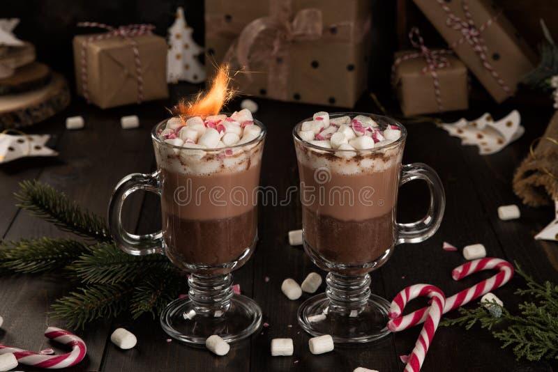 Schale des Kakaogetränks der heißen Schokolade mit Eibische und Wunderkerzen stockbilder