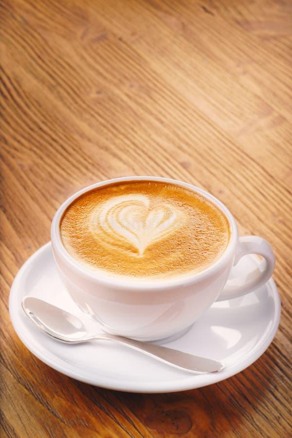 Schale frischer Cappuccinokaffee auf dem Holztisch lizenzfreie stockfotografie