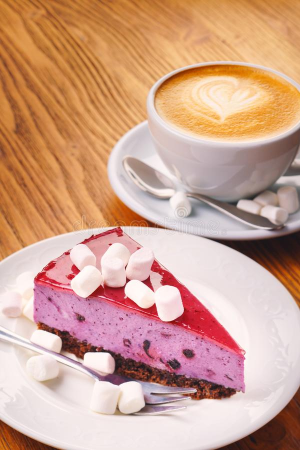 Schale frischer heißer Kaffee mit köstlichem Stück des Blaubeerkuchens auf dem Holztisch stockbild