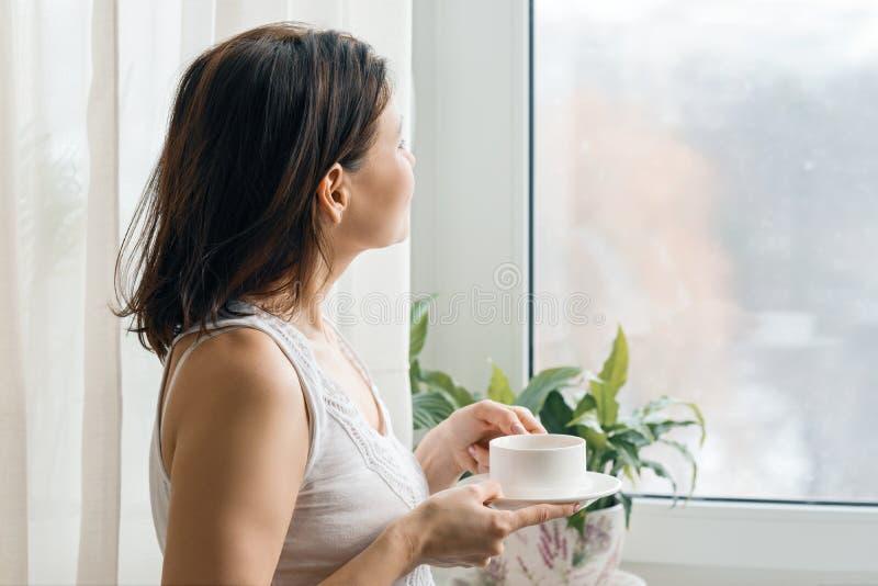 Schale frischer Kaffee des Morgens in den Händen der Frau das Fenster heraus stehend und schauend stockbilder