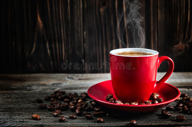 Schale frischer Kaffee mit Kaffeebohnen auf Holztisch lizenzfreies stockbild