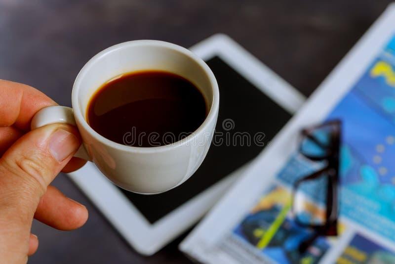 Schale geschmackvoller Kaffee und Zeitungen im Café stockfoto