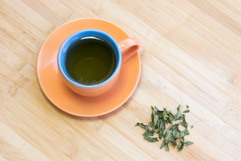 Schale gesunder grüner Tee mit Blättern stockbilder