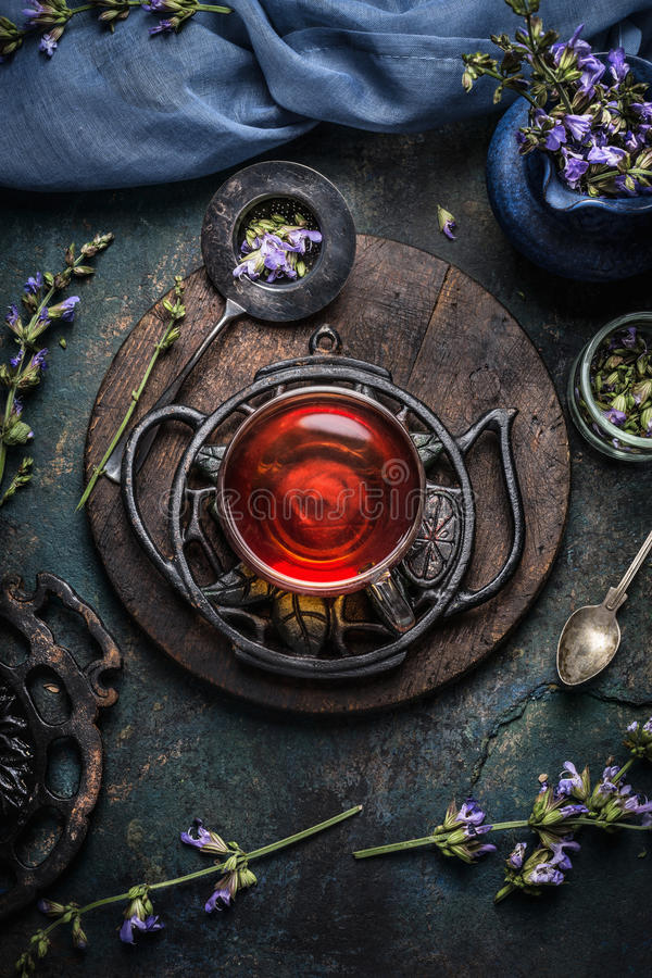 Schale gesunder Kräuterdetoxtee mit Salbeiblättern und -blumen auf dunklem rustikalem Hintergrund, Draufsicht stockfoto