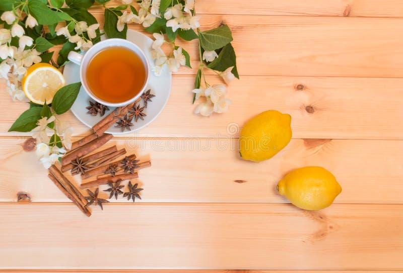 Schale grüner Tee, Zitronen, Gewürze und Jasminblumen lizenzfreie stockfotos