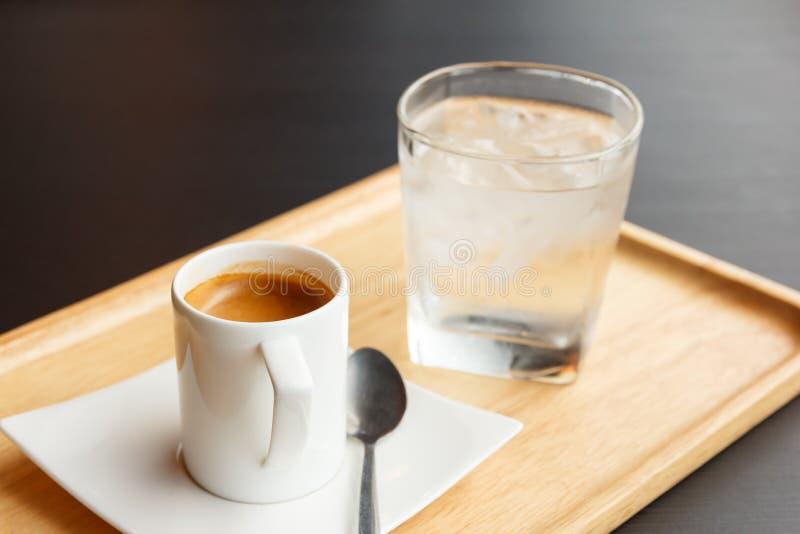 Schale heißer Espressokaffee und Glas kaltes Wasser auf hölzernem tra lizenzfreies stockbild