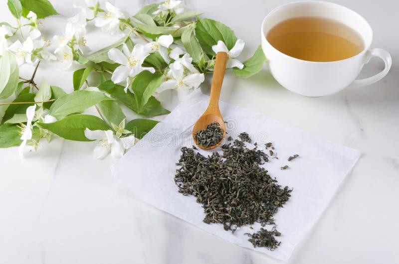 Schale heißer geschmackvoller grüner Tee, Bündel des Jasmins, trockene Blätter des grünen Tees, weiße Marmortabelle lizenzfreies stockfoto