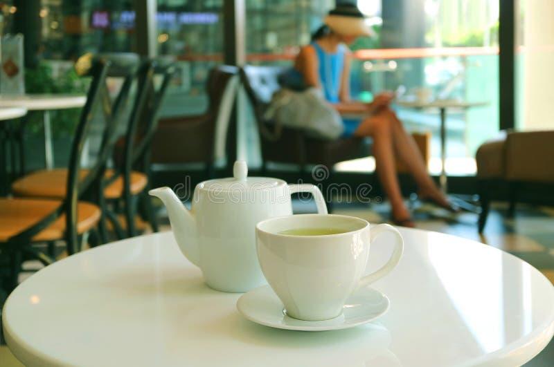 Schale heißer grüner Tee mit Teekanne auf dem weißen Rundtisch des Cafés lizenzfreie stockbilder
