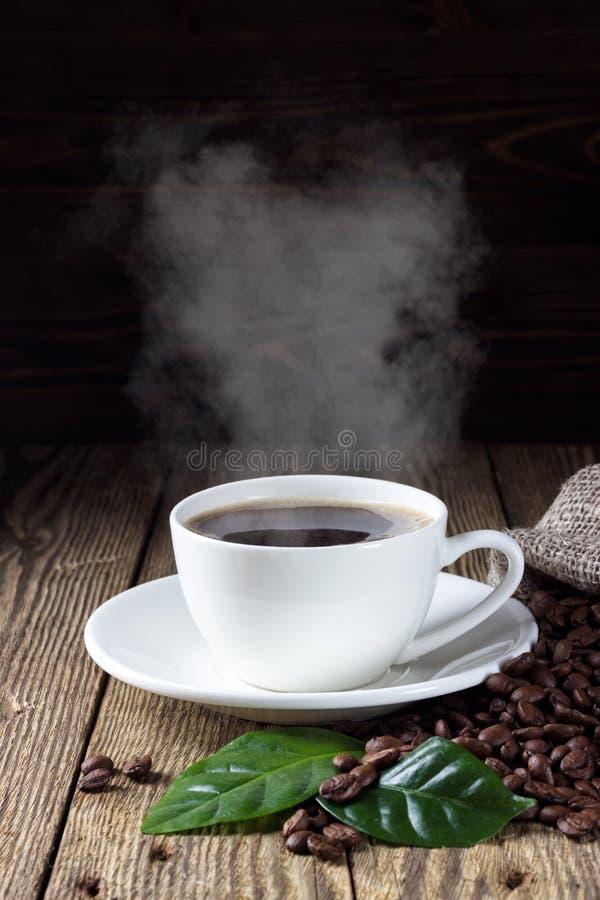 Schale heißer Kaffee mit Kaffeebohnen und Blatt stockbild
