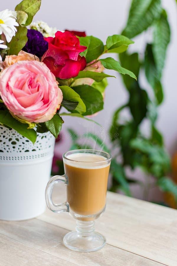 Schale heißer Kaffee mit Milch steht nahe dem Fenster und einem hellen farbigen Blumenstrauß von Blumen stockfotografie