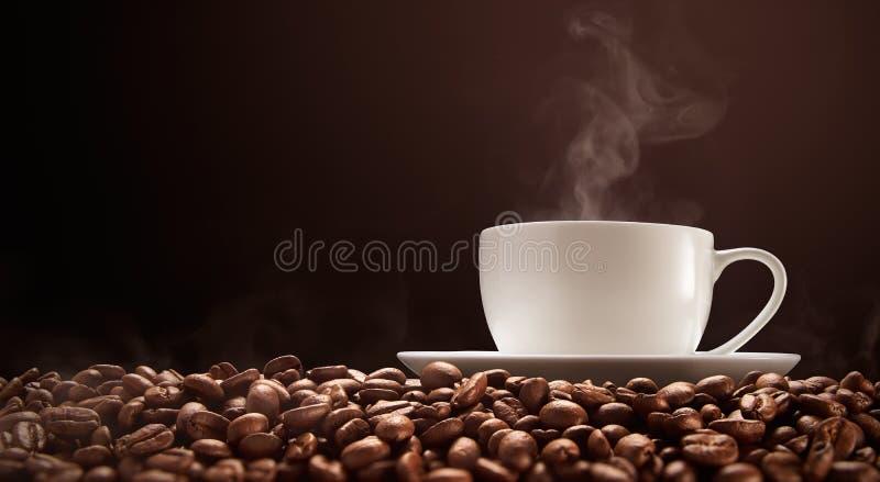 Schale heißer Kaffee mit Rauche auf Kaffeebohnen lizenzfreies stockfoto