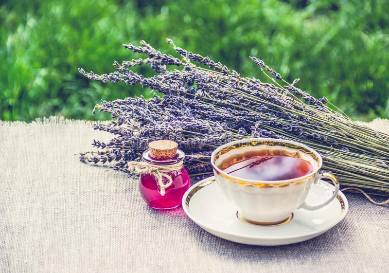 Schale heißes Tee- und Lavendelätherisches öl Naturheilverfahren für Kälten Tee mit Lavendel und Abhilfe Ein heilender Trank lizenzfreies stockfoto