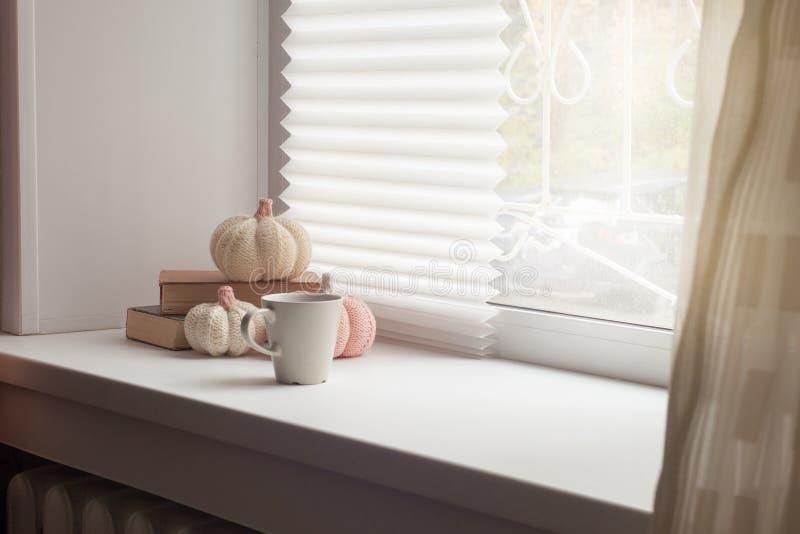 Schale Herbstteekaffee, Schokolade und Bücher und knittted Kürbise nahe einem Fenster, Kopienraum Heißes Getränk für kaltes regne stockfoto